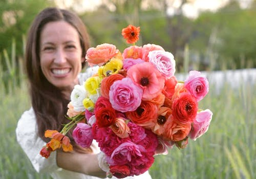 The owner of Eden Roots Flower Farm, holding a bright orange, red, yellow and white bouquet in her field