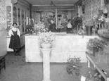 Floral arrangements and plants line the interior of our showroom in the late 1800s