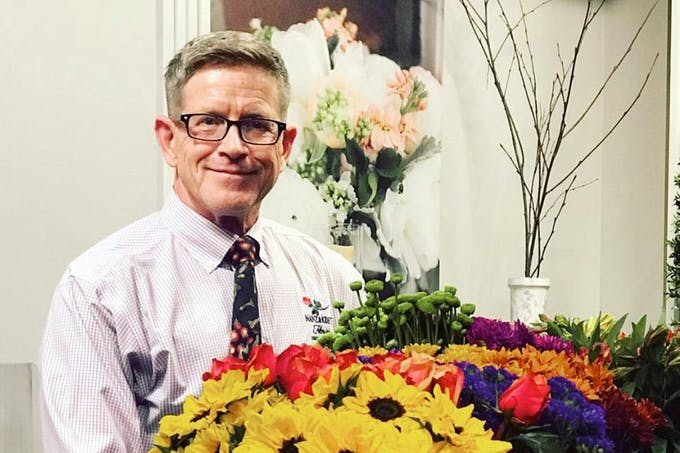 A member of the Nanz & Kraft management team holds a colorful bouquet of red, green, yellow and violet flowers